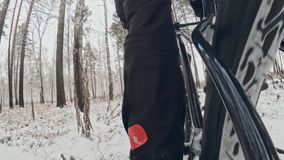 Action cam on frame installed behind. Close-up pov view. Professional extreme sportsman biker riding fat bike in outdoor. S in winter snow forest stock video footage
