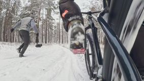 Action cam on frame installed behind. Close-up pov view. Professional extreme sportsman biker riding fat bike in outdoor. S in winter snow forest stock video