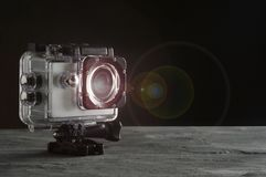 Action camera with lens flare on black background stock photo