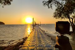 Action camera mounted on a tripod and make a timelapse of the pier and golden sunrise. Focus on the camera.  royalty free stock photos