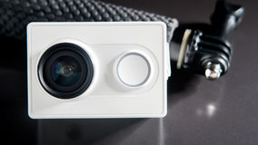 Action camera and small monopod head on black background, selective focus Royalty Free Stock Photo
