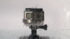 Action camera under rain. Action camera in waterproof case splashed with water stock footage