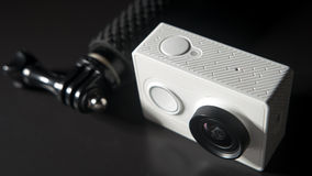 Action camera unrecognasible brand and small monopod head on black background Royalty Free Stock Image