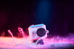 Action camera in waterproof case dropped in powder Stock Photography