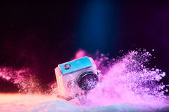 Action camera in waterproof case dropped in powder Stock Image
