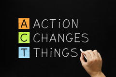 Action Changes Things Acronym. Hand writing Action Changes Things with white chalk on blackboard Stock Image