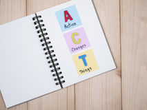 Action, Changes, Things on notebook. Word spelling ACT and handwriting Action, Changes, Things& x22; on white notebook with wood background & x28;Business Stock Images