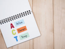 """Action, Changes, Things 1. Word spelling ACT and handwriting Action, Changes, Things"""" on white notebook with wood background (Business concept Stock Photography"""