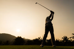 Action de golfeur tandis que coucher du soleil Photo stock