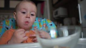 Action drôle avec le bébé qui mange sur la cuisine dans le mouvement lent clips vidéos