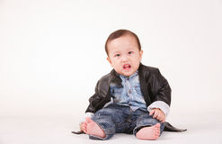 Action fâchée de portrait de bébé garçon dans la veste en cuir, dos de blanc Photos libres de droits
