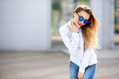 Action fashion portrait of attractive woman in jeans with long hair.Girl in jeans suit.Charming lady with new denim. Outfit. Happy young woman in city street royalty free stock photography