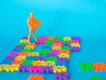Action-Figur-Stand auf buntem Plastikzahl- und Grifforange Plastikzahlschleppseil auf blauem Hintergrund Konzept von Bildung math Lizenzfreies Stockbild