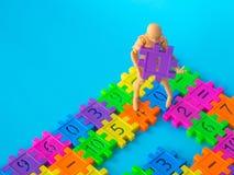 Action-Figur-Stand auf buntem Plastikzahl- und Griffpurpurrotem Plastiknummer eins auf blauem Hintergrund Konzept von Bildung mat Stockfotos
