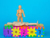 Action figure standing in colorful plastic number and make a headache acting on blue background. Concept of education. copy space. For text and content royalty free stock images
