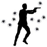 Action hero in gun fight silhouette. Action hero standing and shooting in film styleshoot out action sequence. With bullet holes Stock Photo