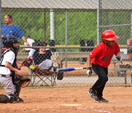 Action at Home Plate. Young batter just dropping his bat (it's suspended in air) after making a hit and heading toward first base. A baseball game of boys 10-12 stock images