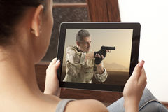 Action  movie on tablet. Cropped image of woman looking at action movie on tablet Stock Photo
