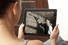 Action  movie on tablet. Cropped image of woman looking at action movie on tablet Royalty Free Stock Photo