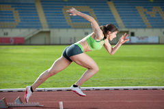 Action packed image of a female sprinter. Leaving starting blocks on the track. Side view Royalty Free Stock Images