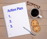 Action plan. Spiral bound notebook with 'Action Plan'  text and blank spaces marked 1,2 and 3, beside the a cup of coffee, biscuits and spectacles Stock Images