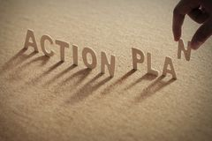 Action plan wood word on corkboard. Compressed board with shadow. alphabets are place on with human finger Stock Photography