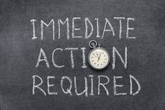 Action required. Immediate action required phrase handwritten on chalkboard with vintage precise stopwatch used instead of O Stock Images