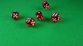 An Action shot of 5 dice thrown onto the table. Action shot of 5 dice thrown onto a table - fast shutter showing dice in the air Royalty Free Stock Photos