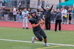 High school football player at end zone. Action shot of a high school football player carrying the football to a touchdown as he approaches the line at the end royalty free stock images