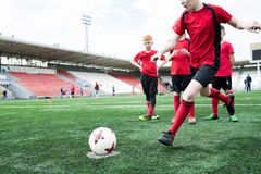 Boy Kicking Ball at Football Practice. Action shot of teenage boy forcefully kicking ball during football match on outdoor stadium, copy space royalty free stock images