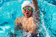Action shot from top of boy swimming backstroke. Close up action portrait of teen boy swimming backstroke.Top view of young swimmer with cap and goggles Royalty Free Stock Photography