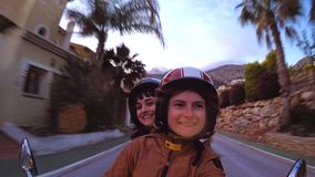 Action shot of two young girls riding scooter. Front view of two cute girl friends or homosexual partners riding motorcycle or scooter on twilight sunset through stock video footage