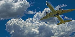 Aircraft in flight with cumulonimbus cloud in blue sky. Australia. An action skyscape view of a commercial passenger jet aircraft flyng closeup in a vibrant royalty free stock image
