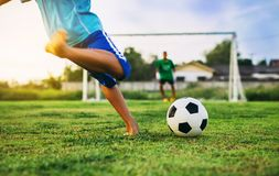 An action sport picture of a group of kids playing soccer football for exercise in community rural area. Kids playing soccer football in the field under the royalty free stock photos