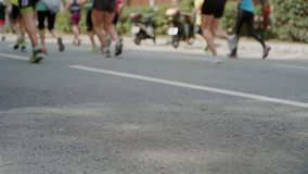 Marathon runners unrecognizable on city street. Action steadycam shot of group or pack or amateur athletes or professional runners during mrathon, unrecognizable stock video footage