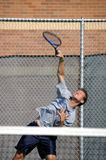 Action on the Tennis Court. Male teen shows extreme effort as he returns a volley during a tennis competition at the high school level.  Grey tee shirt and dark Royalty Free Stock Photos