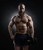 Actionnez l'homme barbu sportif dans la formation pompant muscles avec d photos stock