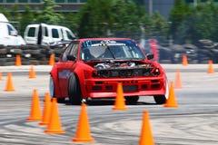 Actionnez la dérive de la voiture de course entre les cônes du trafic Photographie stock libre de droits
