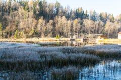 Actionnez la maison par le lac givré d'hiver illuminé par le Soleil Levant Photographie stock libre de droits