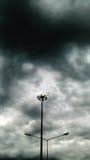 Actionnez le pilier électrique et le nuage foncé en ciel Photographie stock