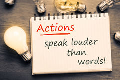 Actions Speak Louder. Than Words text on notebook with many light bulbs Stock Photos