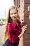 Actitud adolescente femenina joven de la muchacha contra una pared de ladrillo Imágenes de archivo libres de regalías
