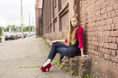 Actitud adolescente femenina joven de la muchacha contra una pared de ladrillo Fotografía de archivo libre de regalías