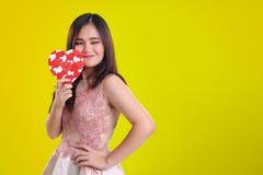 Actitud alegre de la señora con la caja en forma de corazón para la tarjeta del día de San Valentín Foto de archivo libre de regalías