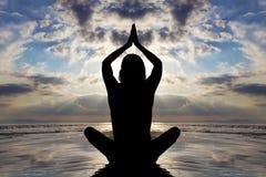 Actitud asentada de la yoga por el océano. Imagenes de archivo