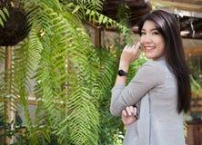 Actitud asiática de la mujer en el café al aire libre adulto femenino joven con natura Imagen de archivo