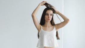 Actitud atractiva hermosa a cámara lenta de la muchacha en cámara y smililng Pruebas modelo en estudio metrajes