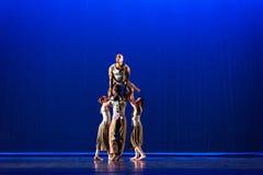 Actitud de cuatro bailarines contra fondo azul marino en etapa Imágenes de archivo libres de regalías