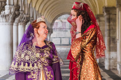 Actitud de dos mujeres debajo de arcos de los duxes palacio, carnaval de Venecia Fotografía de archivo