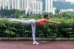 Actitud de equilibrio horizontal practicante profesional del palillo de la yoga del atleta de sexo femenino que se coloca en una  Foto de archivo libre de regalías